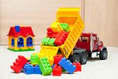 stock photo of dumper  - Dump truck toy downloading colorful toy blocks - JPG