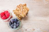 Healthy Background: Wooden Table With Granola Cereals Bars And Small Jars Full Of Berries
