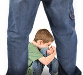 stock photo of abused  - A young boy is sitting on the ground and scared - JPG
