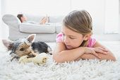 Little girl lying on rug with yorkshire terrier at home in the living room