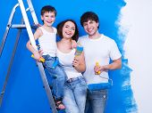 Portrait of happy young family standing together with paintbrush and stepladder