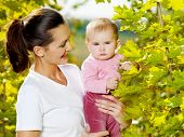 Beautiful happy mather with attractive baby outdoor, on nature