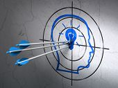 Business concept: arrows in Head With Lightbulb target on wall background