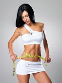 Slim woman and measure tape around her body - a studio shot