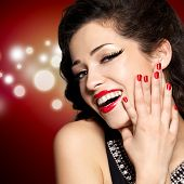 Beautiful woman with red manicure and  lips.  Fashion model with bright positive emotions. Blinking Background. Bokeh
