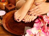 Closeup photo of a female feet at spa salon on pedicure procedure. Female legs in water decoration