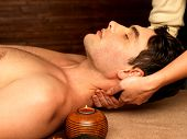Masseur doing neck massage on man in the spa salon.