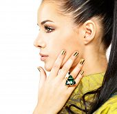 Pretty woman with golden nails and beautiful precious stone emerald - isolated on white background