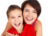 Happy laughing young mother with son 8 year old over white background
