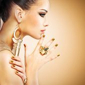 stock photo of brunette  - Profile portrait of the beautiful fashion woman with black makeup and golden manicure - JPG