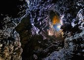 Colorful light in a dark cave with limestone formations