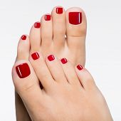 stock photo of pedicure  - Closeup photo of a beautiful female feet with red pedicure isolated on white - JPG
