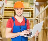 Portrait of smiling handyman with laptop working warehouse