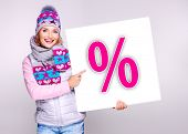 Adult smiling  woman in warm outerwear  holds the white banner with per�?�?�?�ent symbol on it