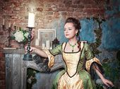 Beautiful Woman In Medieval Dress With Burning Candle