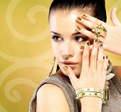 stock photo of minx  - Pretty woman with golden nails and beautiful gold ring over creative background - JPG