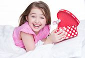 Portrait of little happy girl with a gift lying on the bed - isolated on white.