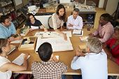 pic of pacific islander ethnicity  - Female Boss Leading Meeting Of Architects Sitting At Table - JPG