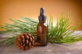 Bottle of pine essential oil on wooden board