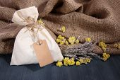 Textile sachet pouch with dried flowers, herbs on wooden table, on sackcloth background