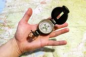 Compass In The Hand With Map Of The Area