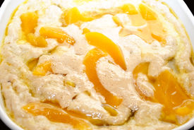 picture of doughy  - A Close Up of a Casserole Filled with Raw Peach Cobbler - JPG