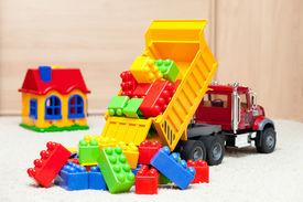 stock photo of dumper  - Dump truck toy downloading colorful toy blocks - JPG