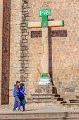 CUZCO, PERU, MAY 1, 2014:  Local couple pass by the cross in front of San Francisco church