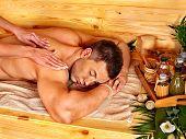 Man getting massage in bamboo spa. Female therapist.