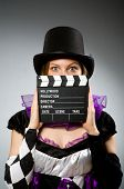 Woman with movie clapboard against grey background