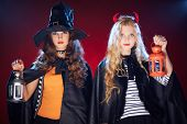 Halloween girls in black cloaks holding lanterns