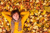 Curly Man In Yellow Sweater And Scarf Lie On Autumn Leaves