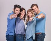 happy group of casual people pointing fingers to the camera on grey background