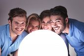 young casual people with faces close to a big ball of light and smile to the camera