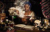 Female alchemist preparing green liquids in a smoking kettle