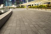 pavement on the roof of building and cityscape at night
