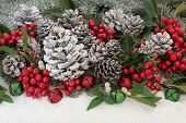 Traditional christmas background with holly, ivy, mistletoe, fir and pine cones and bauble decorations with snow.