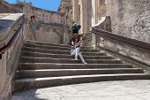 DUBROVNIK, CROATIA - MAY 28, 2014: Japanese tourists sitting on Jesuits staircase, the grand stairca