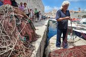 DUBROVNIK, CROATIA - MAY 26, 2014: Local fisherman in city port holding fishing net. Thanks to local fishermen Dubrovnik is brimming with fresh seafood.