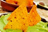 closeup of a bowl with guacamole and nachos dipped in it