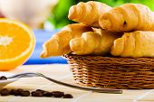 Croissants and cup of coffee on breakfast table