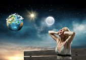 Young woman sitting on bench closing ears with palms and screaming. Elements of this image are furnished by NASA