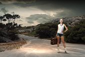 Young woman hiker standing with suitcase in hand