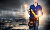 Young pretty woman engineer with tool belt on waist