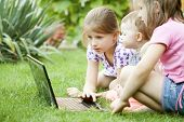Curious kids with laptop computer laying in the grass