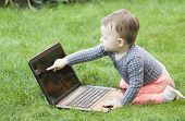 Curious baby with laptop computer laying in the grass