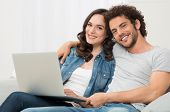Happy Young Couple Sitting On Couch With Laptop