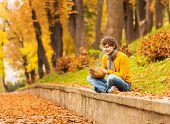 Curly Man With Computer Tablet In Autumn Park