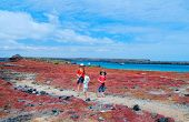 Mother and two kids hiking on Galapagos island of South Plaza