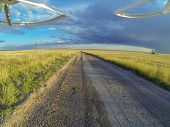 aerial view from a quadcopter drone landing on a dirt road in Pawnee National Grassland with windmil